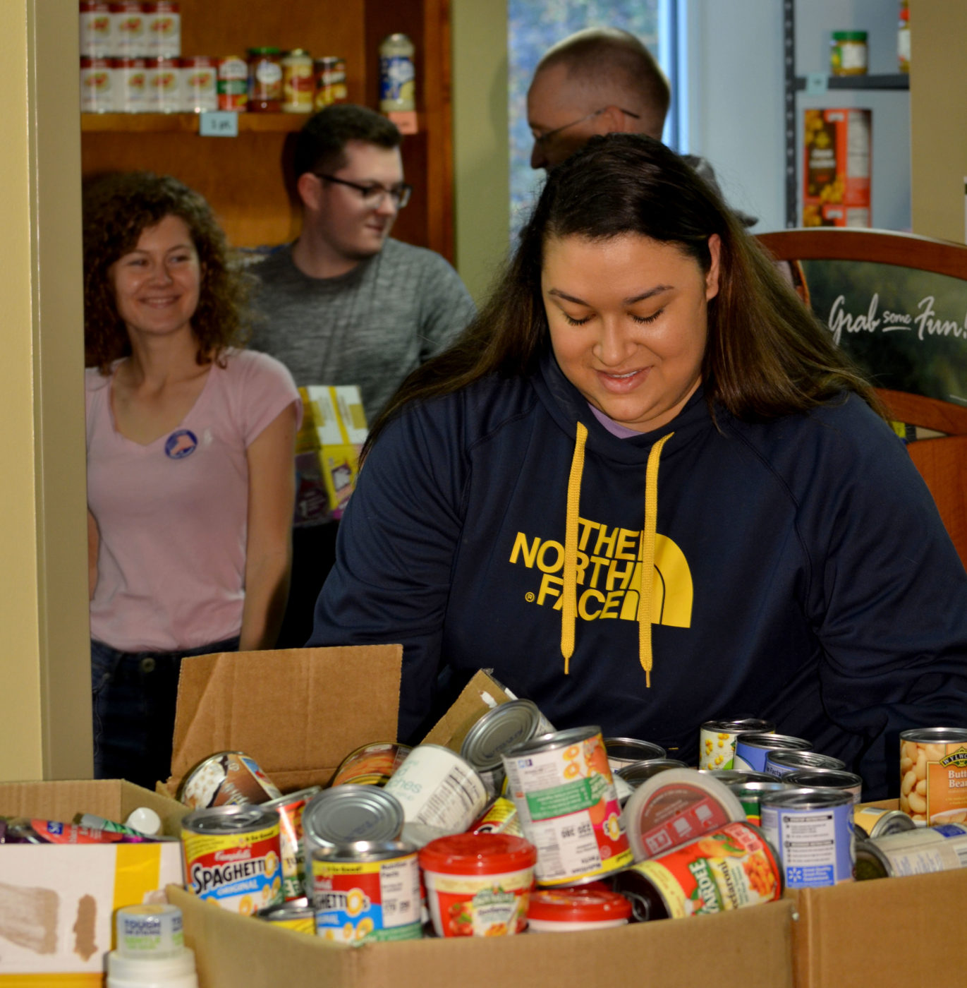 Volunteers help to sort and shelve food pantry stock at Patrick Henry Community College.